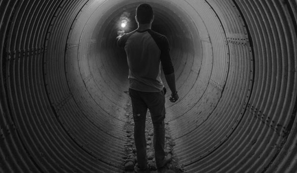 man with light in dark tube exploring to find a way out